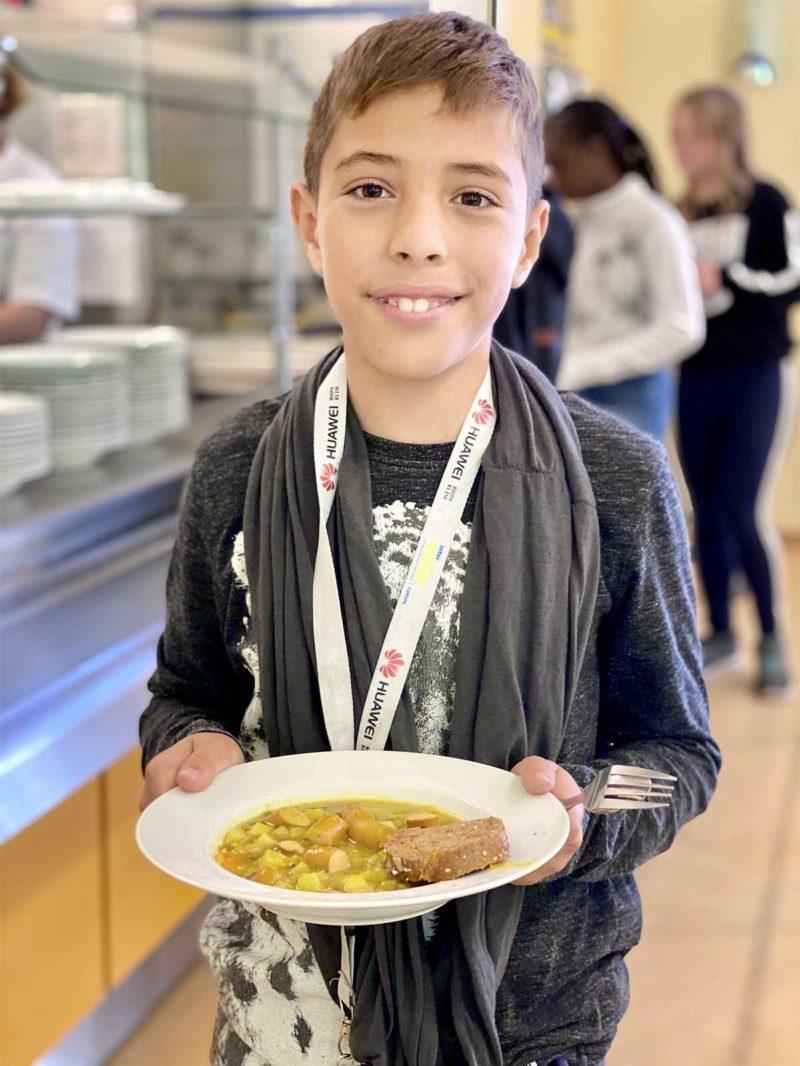Junge mit Essen in Mensa